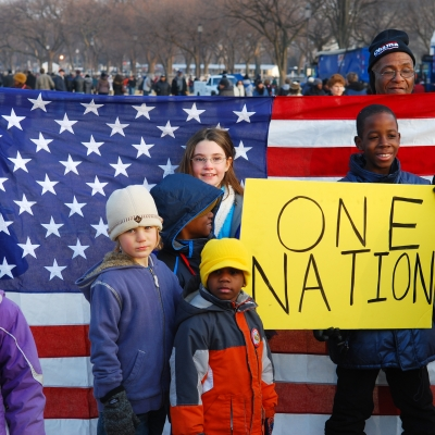 """three Black children, three white children and two Black adults are posing. One of the Black boys is holding a protest sign that says """"one nation"""" while the adults in the background hold an American flag."""