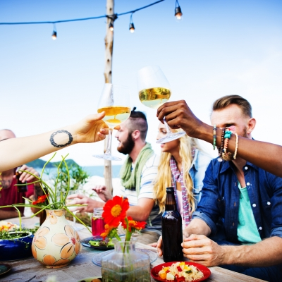 multiracial group of people sharing a meal, toasting with wine glasses