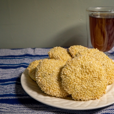 plate of cookies covered in sesasme seeds with cup of tea in the background on blue and white striped tablecloth