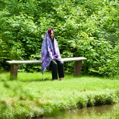 Rabbi Vivie Mayer is sitting on a bench in a green field next to a lake with a tallit covering her head.