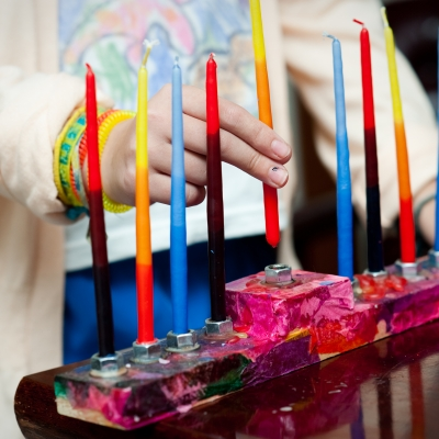close up of child putting colorful candles in menorah