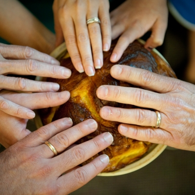 hands touching a round challah