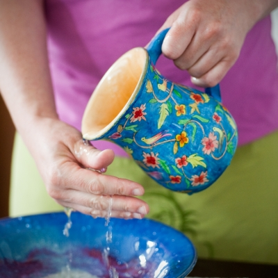 woman washing hands into a bowl with ceramic ritual hand-washing pitcher
