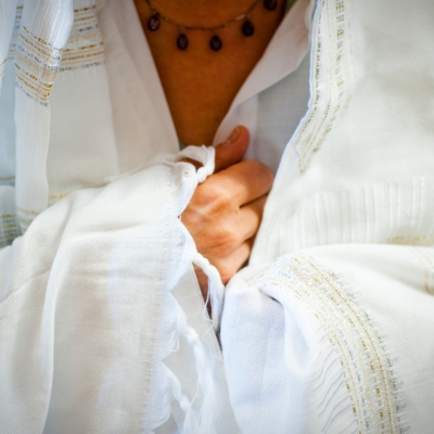 Vivie Mayer is pictured from just below the neck to the middle of her torso. She is drapped in a white tallis and is clutching the corners and holding them close to her heart. Around her neck is a chain necklace with purple stones hanging from it.