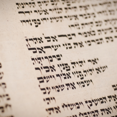 A section of the torah scroll is pictured. On it is one of the Hebrew names for God.