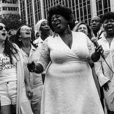 Resistance Revival Chorus members wearing white and singing in the streets