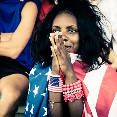 a black woman is sitting with her hands together , draped in an american flag and wearing patriotic bracelets on both arms.