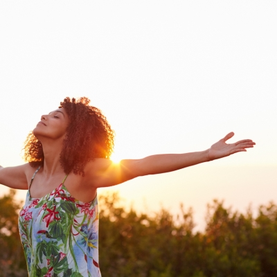 black woman with arms spread out into the sunshine
