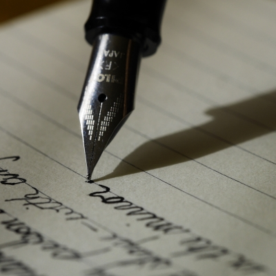 a ink pen presses against a piece of paper. There is script on the lines ahead of the pen.