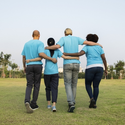 four people of different races with arms around each other