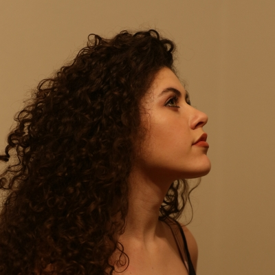 The profile of person with long curly brown hair is pictured. There is red lipstick on their lips.
