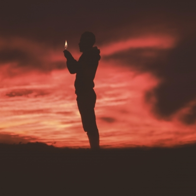 silhouette of person holding candle in dark landscape with reddish and dark clouds all around