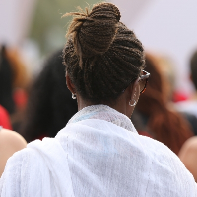 A Black woman shown from behind in a crowd of people wearing white shawl