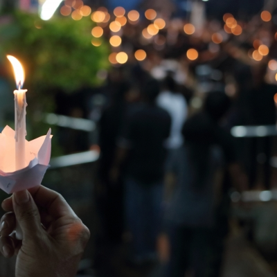 foreground hand holding thin white lit candle, background people gathered and other candles lit, blurry