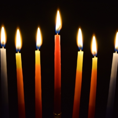 eight hanukkah candles and one shamash are lit against a black background