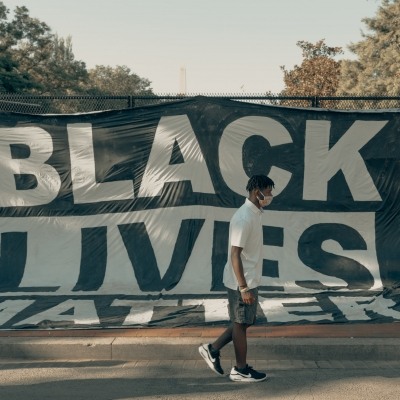 A banner with Black Lives Matter hangs over a fence. Walking in front is a Black man in dark pants and a white shirt wearing a mask.