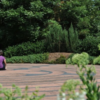 woman sitting in a labyrinth outdoors