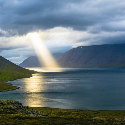 a white stream of light shines through the clouds onto a body of water in between two mountains