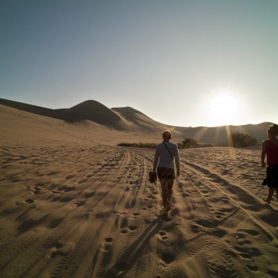 two people walking in desert with sun shining above