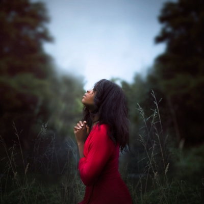 a black woman stands in the middle of a field of trees. She is wearing a read dress and her hair is long and dark. Her hands are clasped in front of her chest and her head is tilted up toward the sky in a prayer stance.