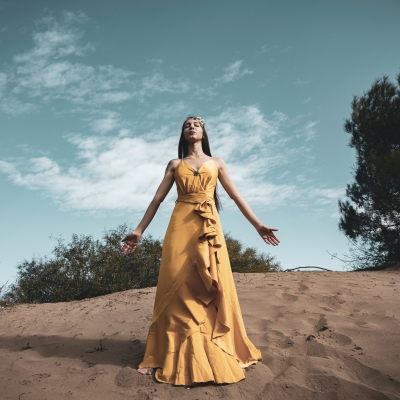 woman in mustard yellow dress standing sandy open space with trees sky clouds in the background, her arms open at her sides, eyes closed, head reaching to sky