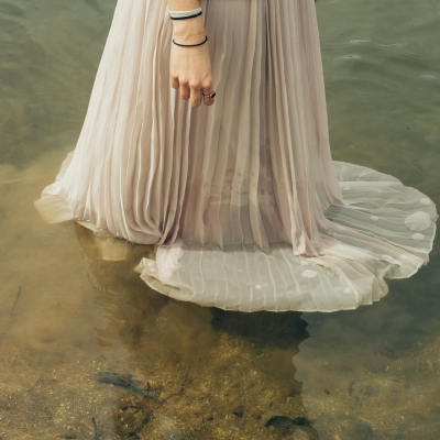 woman in white gown walking in water