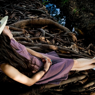 woman sitting on branches outside