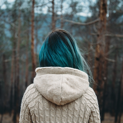 girl with blue hair facing forest