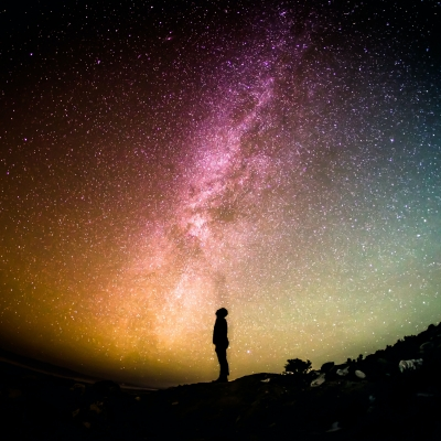 the silhouette of a person is pictured in the center of the image. In the background is a multi-colored night sky with stars and clouds and planets visible