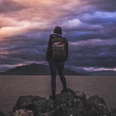 person hiking, facing storm clouds
