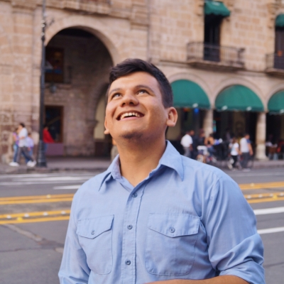 Latinx person wearing a blue collard button down shirt walking on a city street smiling up at the sky