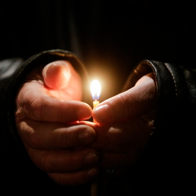 hands holding single lit candle