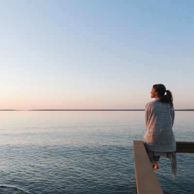woman sitting on dock looking out into the ocean