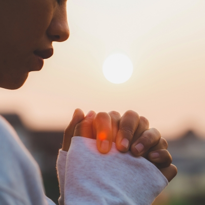brown-skinned woman with hands clasped and head bowed with sun in background