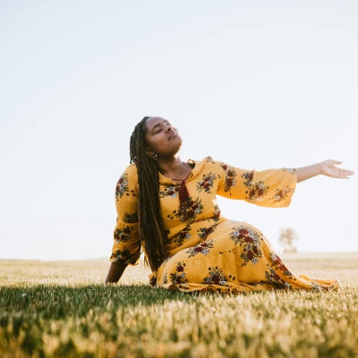 black woman in yellow patterned dress sitting in sunny field smiling hand open to sky