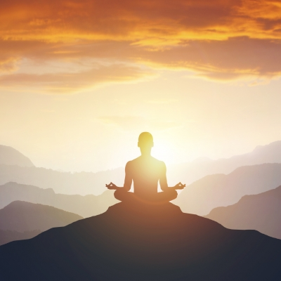 silhouette of person meditating on mountain top. clouds above and mountains in the distance. sun shining behind person's body.