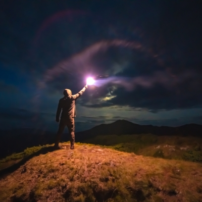 person standing in field in the dark holding a spark up to the sky