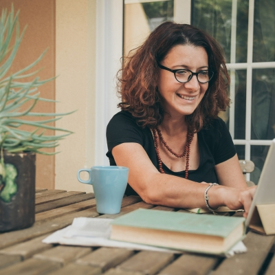 middle aged light skinned woman with black frame glasses sitting at desk in front of ipad smiling