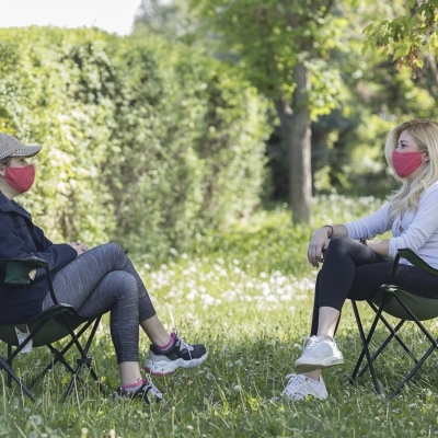 two women wearing masks sitting in chairs on a lawn six feet apart, looking at each other and chatting