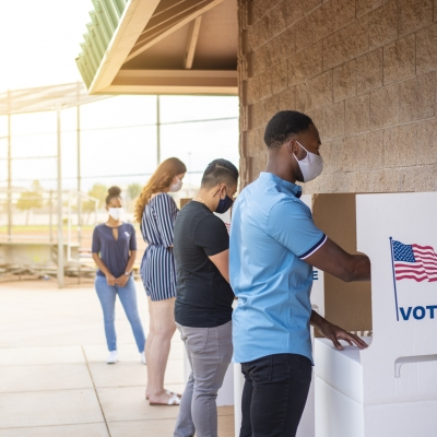 three people are standing in a row at ballot boxes outdoors, voting. All three are wearing masks while a poll worker watches in the background also wearing a mask. We can see the side of the ballot station of the first person. It says vote with an American flag.