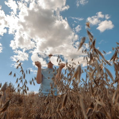 A boy with two round mirrors, in which the sky is reflected in glasses, stands in a field of wheat stock photo
