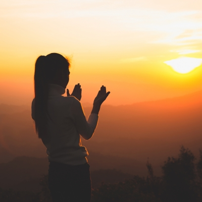 woman shown in silouhette on a mountain looking at sunset with hands open as if in prayer