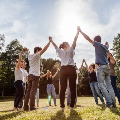 group of people holding hands lifting arms to sky in a sunlit field