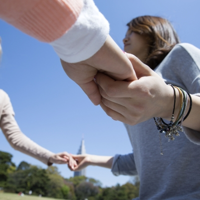 people in a circle holding hands outdoors
