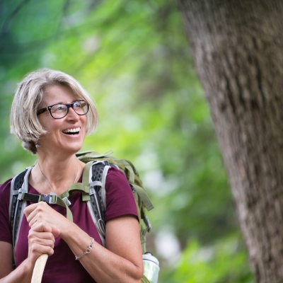 woman in a forest with backpack on, smiling
