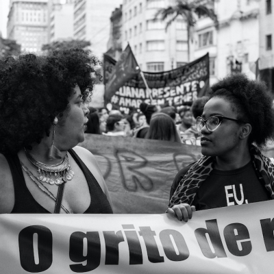 two black women at a protest holding a banner