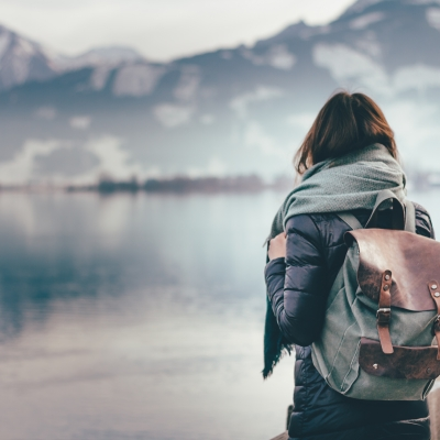 woman wearing backpack facing lake and mountains