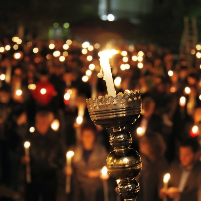 candle lifted up in the foreground, sea of candles in the background