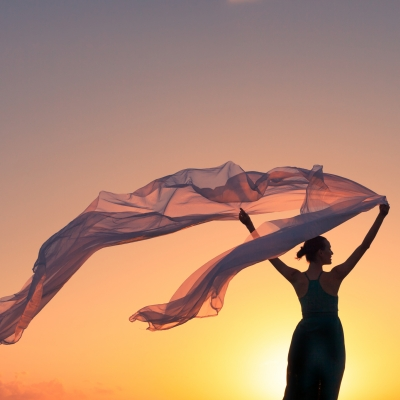 silhouette of woman holding flowing white silk fabric against sunset