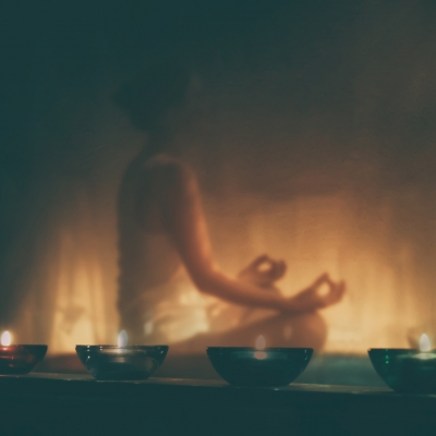 person meditating by candlelight